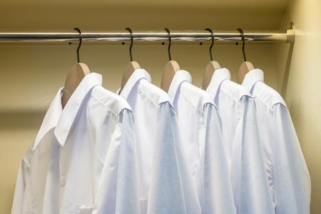 tela blanca: cerca de camisas blancas colgando de gancho de ropa en el armario Foto de archivo