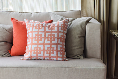 deep orange: Chinese pattern  in orange and deep orange and gray pillows on light gray sofa set Stock Photo