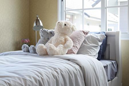 cama: habitación de los niños con muñecas y almohadas en la cama y la mesita de luz de la lámpara