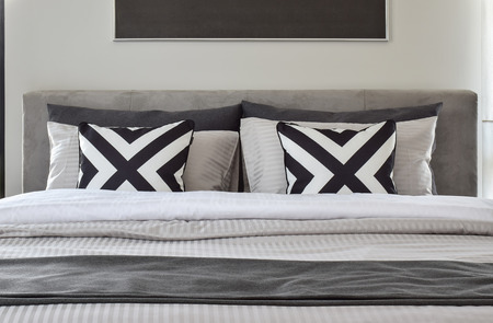 bed: Graphic patern pillows with modern classic style bedding