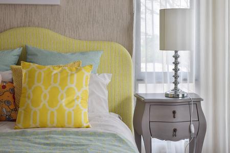 cama: Almohadas amarillas y verdes y el patrón en la cama de estilo clásico y lámpara de lectura en mesilla de noche