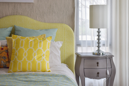 bed: Yellow and green and pattern pillows on classic style bed and reading lamp on bedside table