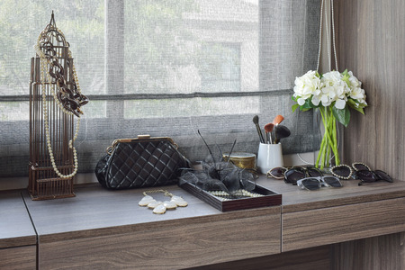 handbag,sunglasses,jewelry and makeup brushes on a wooden dressing table Foto de archivo