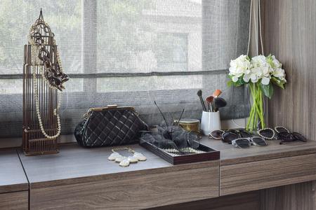 handtas, zonnebrillen, sieraden en make-up kwasten op een houten kaptafel Stockfoto