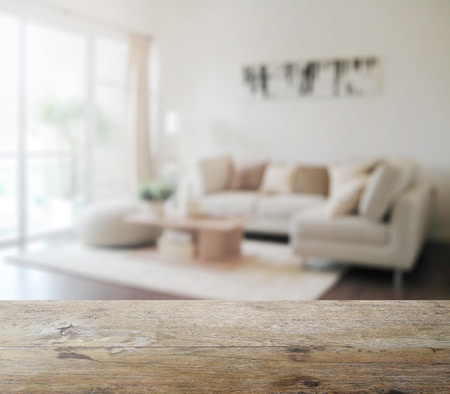 comfortable home: wooden table top with blur of modern living room interior as background