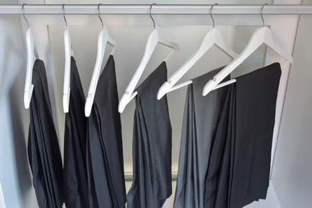 row of gray and black pants hangs in wardrobe at home Zdjęcie Seryjne - 44563406