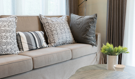 sturdy: Sturdy brown tweed sofa with grey patterned pillows