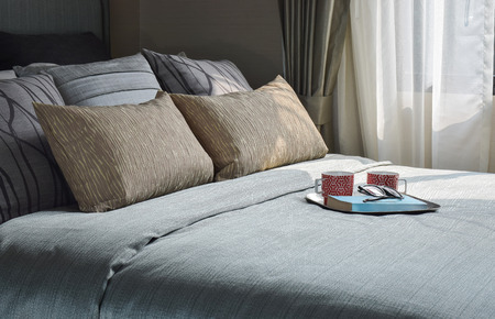 Mugs and book are on the romantic bedding style Stock Photo