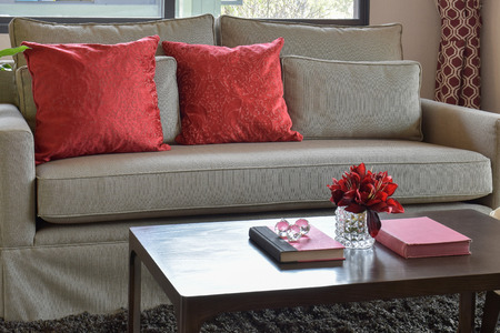 red pillows: comfortable sofa with red pillows and red book on wooden table in living area at home