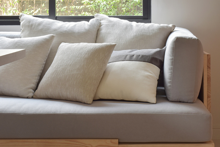 comfy: Beige varies size pillows setting on light gray comfy sofa