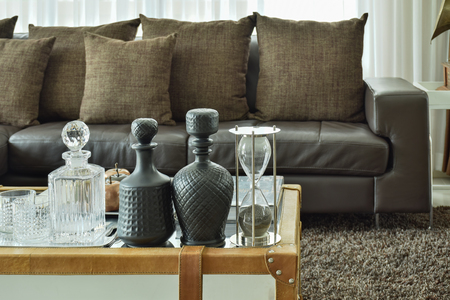 sitting on sofa: Crystal drink set and sandglass on glass top table with wooden frame and dark brown sofa set in the living room