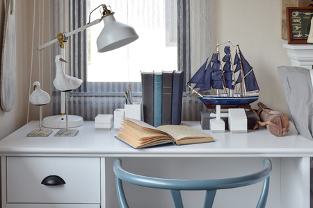 working area: white table with wooden chair books and lamp in modern working area at home
