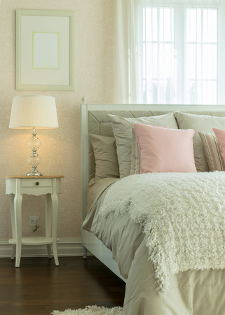 reading lamp: luxury bedroom interior with pink pillows and reading lamp on bedside table Stock Photo