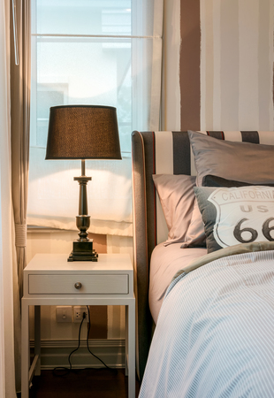 bedside lamp: cozy bedroom interior with dark brown pillows and reading lamp on bedside table