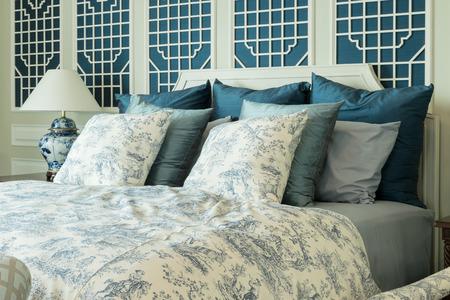 klassischen Stil Schlafzimmer mit blauen Kissen und chinesische Lampe Stil auf dem Nachttisch