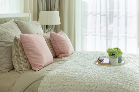 bedroom interior: luxury bedroom interior with pink pillows and white tray of flower on bed Stock Photo
