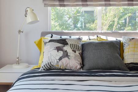 cama: interior del dormitorio con estilo en blanco y negro con almohadas estampadas en la cama y la lámpara de tabla decorativa.