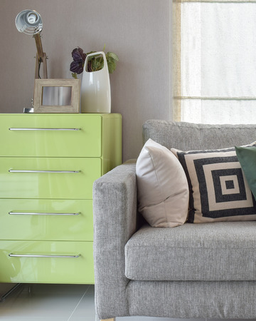 green sofa: Cozy sofa with geometric pattern pillows and green sideboard in living corner
