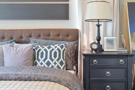 El interior comodo dormitorio con almohadas y lámpara de lectura en la mesa junto a la cama Foto de archivo - 46008064