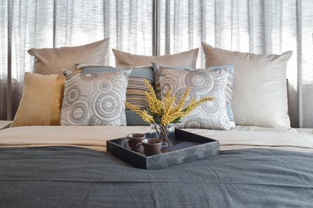 ストライプ枕とベッドの上の装飾的なお茶セット豪華なベッドルームのインテリア デザイン