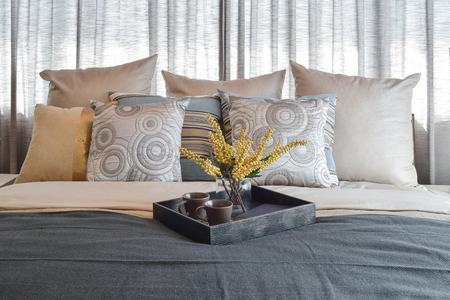 bedding: luxury bedroom interior design with striped pillows and decorative tea set on bed