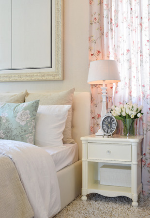 table lamp: vintage bedroom interior with decorative table lamp, alarm clock and flower on white table Stock Photo