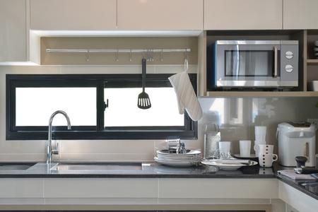 Steengoed en gebruiksvoorwerpen opzetten naast de gootsteen in moderne keuken Stockfoto