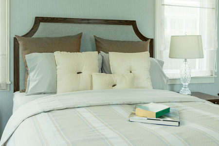 reading lamp: cozy bedroom interior with white pillows and reading lamp on bedside table