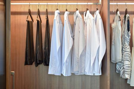wardrobe closet: row of white shirts hanging in wooden wardrobe Stock Photo