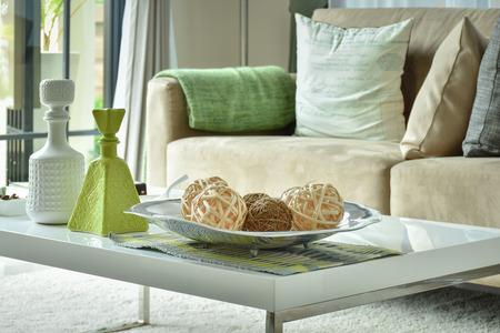 ラットン ボールと光で白いテーブルに花瓶が茶色のソファ 写真素材
