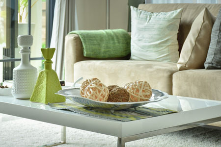 Ratten ballen en vazen op witte tafel met licht bruine bank Stockfoto