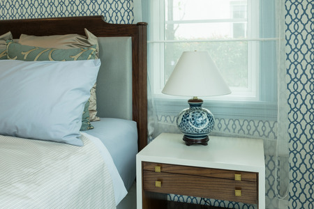 bedside lamp: classic style bedroom with blue pillows and chinese lamp style on bedside table