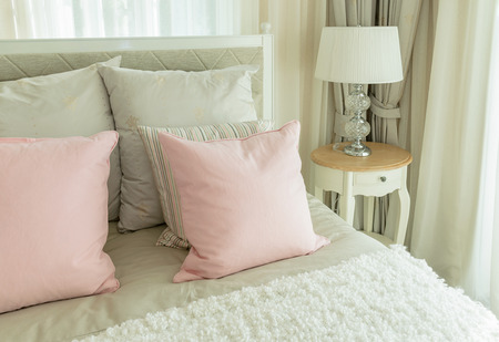 bedside lamp: cozy bedroom interior with pink pillows and reading lamp on bedside table