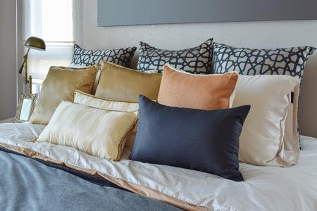 naranja: Interior del dormitorio moderno con cojines naranjas y oro sobre la cama y la mesita de noche de la l�mpara