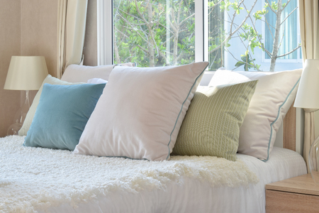 white pillow: stylish bedroom interior design with colorful pillows on bed and decorative table lamp.