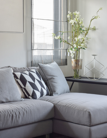 apartment interior: Parallelogram pattern pillow and gray pillows setting on gray sofa at comfortable living corner