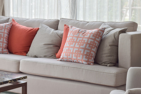 sofa: Chinese pattern pillow, red and gray pillows setting on light gray comfy sofa