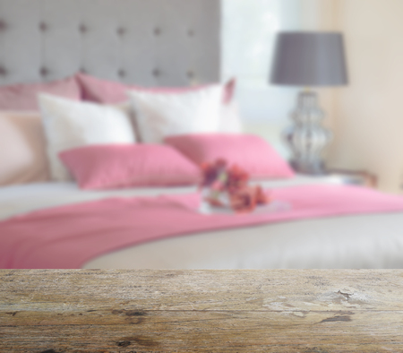 red bed: wooden table top with blur of red bed and pillows in modern bedroom as background