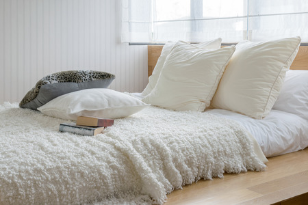 to white: sylish bedroom interior design with black and white pillows on bed. Stock Photo
