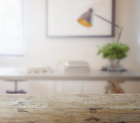 wooden table top with blur of modern working table with book and lamp as background
