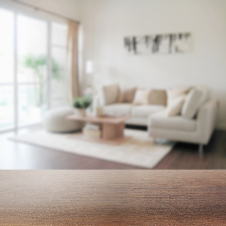 wooden table top with blur of modern living room interior as background