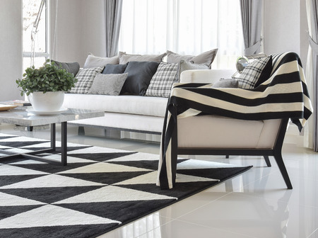 modern lifestyle: modern living room interior with black and white checked pattern pillows and carpet Stock Photo