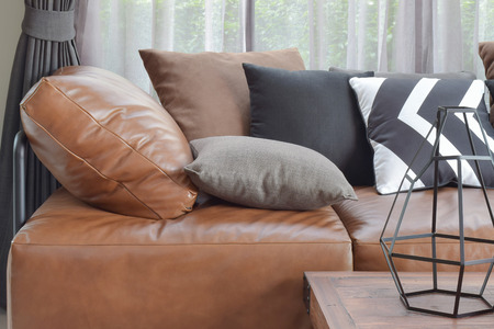 couch: Light brown leather sefa bed with varier color and size pillows