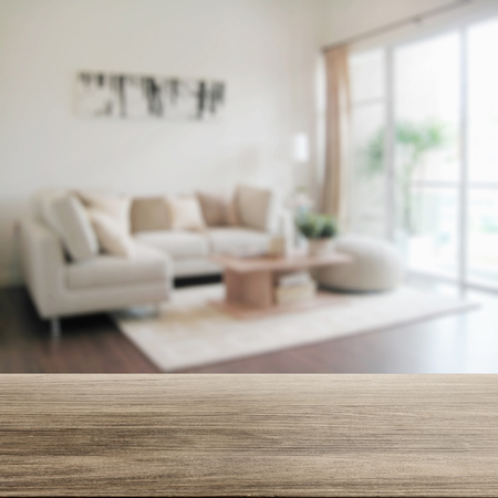 wooden table top with blur of modern living room interior Stock Photo