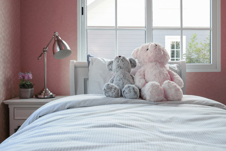 bedside: kids room with dolls and pillows on bed and bedside table lamp