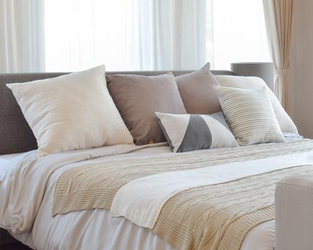 ベッド、装飾的なテーブル ランプに茶色のパターン化された枕でスタイリッシュなベッドルームのインテリア デザイン。