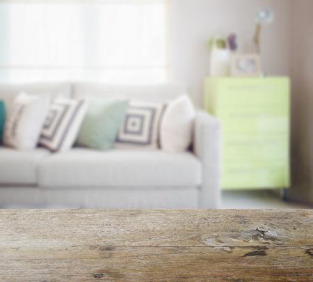 Tischplatte aus Holz mit Unschärfe der geometrischen Muster Kissen auf gemütliches Sofa und grüne Anrichte im Wohnzimmer