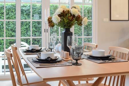 dining room: wooden table and chairs in dining room with elegant table setting