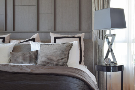 bedside lamp: stylish bedroom interior design with black patterned pillows on bed and decorative table lamp. Stock Photo