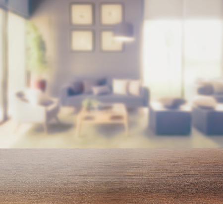 wooden table top with blur background of modern living room interior Standard-Bild